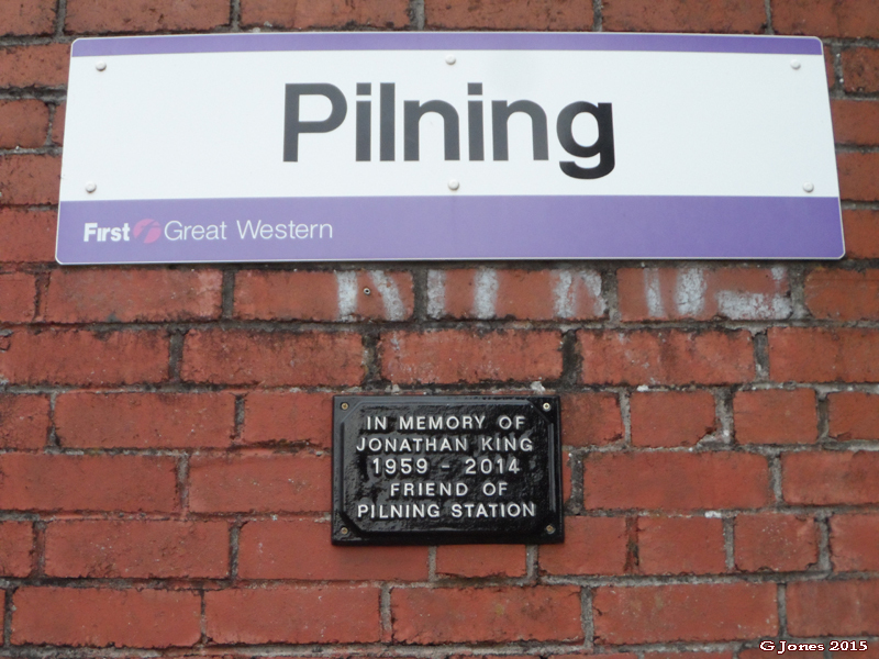 "A picture, showing the Pilning running-in board branded First Great Western. Underneath is the memorial plaque commemorating Jonathan King. The plaque reads, ""In memory of Jonathan King. 1959-2014. Friend of Pilning Station."""